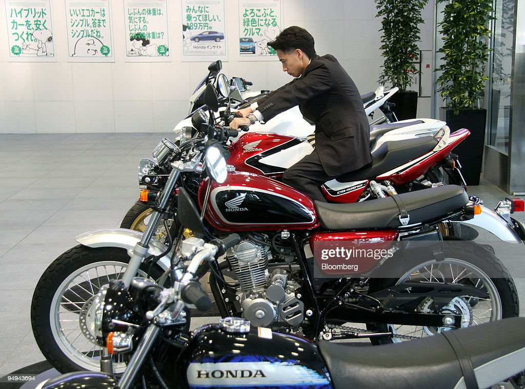 A Man Looks At Honda Motor Co CB400 Super Four Motorcycle The Companys