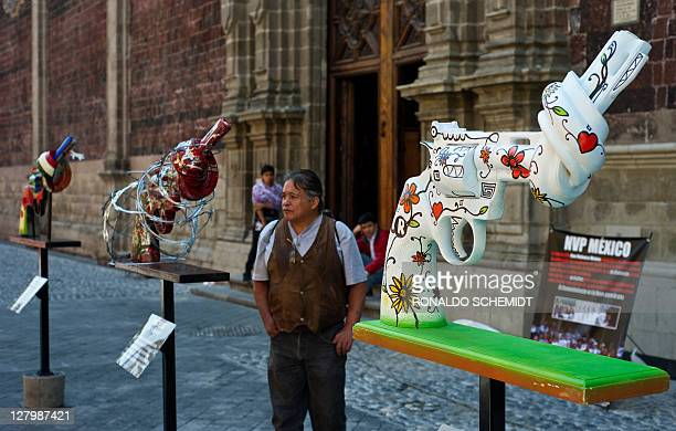 Man looks at a knotted gun-shaped sculpture in Mexico City, on October 4, 2011. Six giant guns with a tied barrel --to stop bullets-- including a...