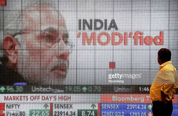 A man looks at a large screen showing television coverage of Narendra Modi prime ministerial candidate of the Bharatiya Janata Party during the...