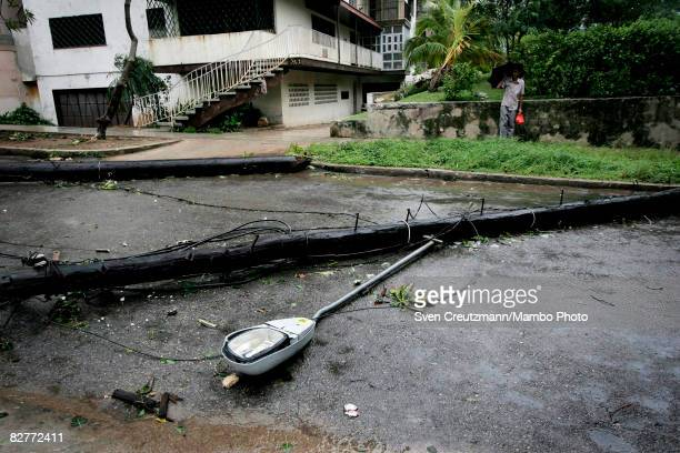 Man looks at a light post that was knocked down by heavy winds following the passing of Hurricane Ike in the Jesus del Monte hill, 10 de Octubre...
