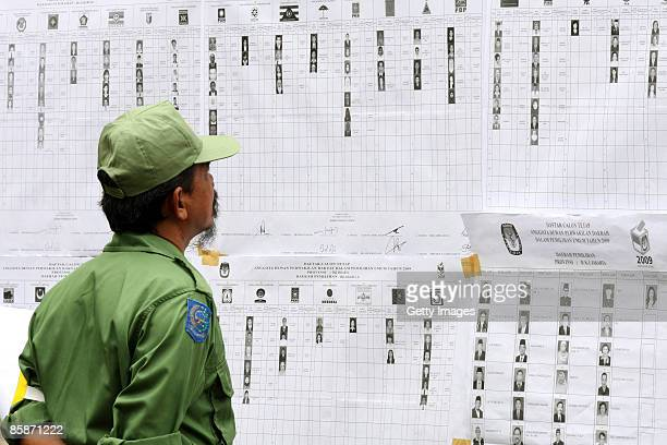 A man looks at a list of legislative candidates during Indonesia's Legislative Elections at a polling booth on April 9 2009 in Jakarta Indonesia The...