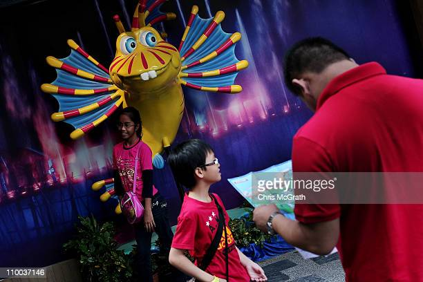 A man looks at a map as his family poses for photographs with an attraction on Sentosa Island on March 13 2011 in Singapore Asia is currently...