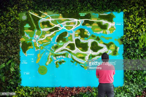 A man looks at a map of Malaysia and Singapore inside a showroom at the Country Garden Holdings Co Forest City Industrialised Building System...