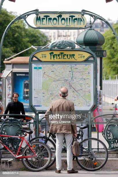 A man looks at a map of the Paris subway lines at the entrance of the metro station 'Pasteur' on May 22 2017 in Paris France The entrance to this...