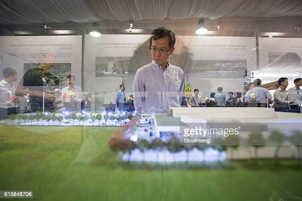 A man looks at a model of Seletar Airport's new passenger terminal during a groundbreaking ceremony in Singapore on Thursday Oct 20 2016 The...