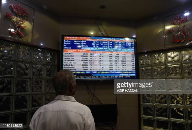 A man looks at a monitor showing share prices during a trading session at the Pakistan Stock Exchange in Karachi on August 7 2019