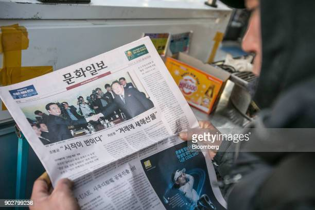 A man looks at a newspaper featuring a photograph of Cho Myounggyon South Korea's unification minister left shaking hands with Ri Son Gwon chairman...