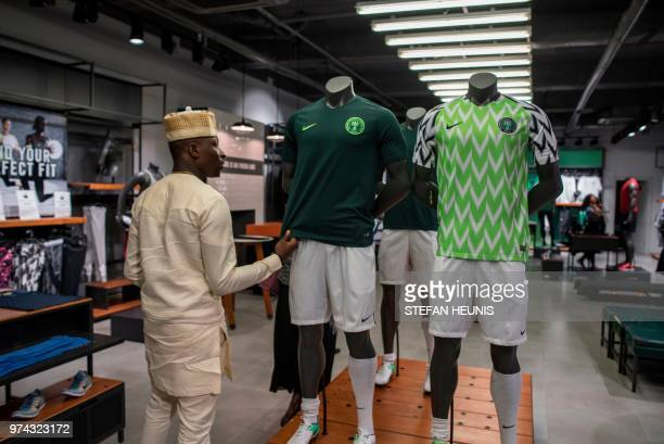 A man looks at a Nigerian World Cup jerseys in a Nike store in Lagos on June 4 2018 The Nigeria Super Eagles jersey for the 2018 World Cup in Russia...