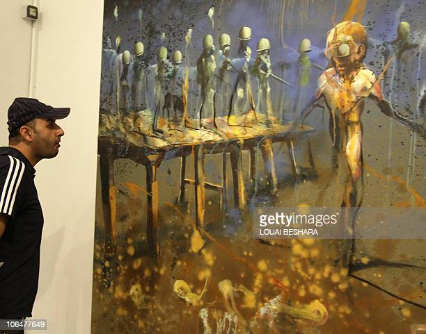 A man looks at a painting at an exhibition by the Norwegian artist Haakon Gullvaag entitled Terra Sancta on display at the French Cultural center in...