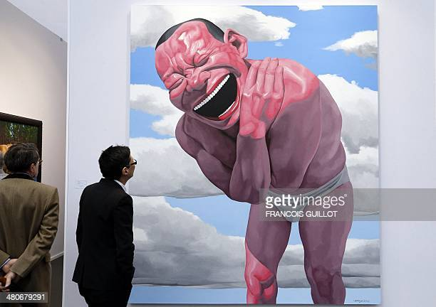 A man looks at a painting by Chinese artist Yue Minjun known as 'Blue sky and white clouds' during the 'Art Paris Art Fair' in Paris on March 26 2014...