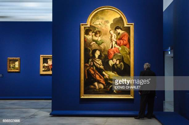 A man looks at a painting by French painter Louis Le Nain presented during the exhibtion 'Le mystere Le Nain' at the LouvreLens in Lens northern...