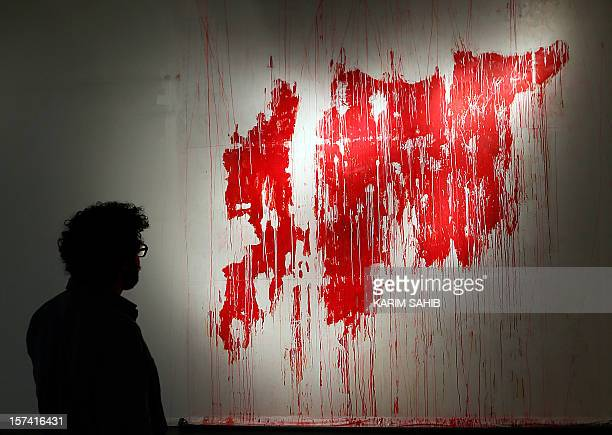 A man looks at a painting depicting a map of 'bleeding' wartorn Syria part of an exhibition titled 'The Syrian Museum' on show in Dubai on November...