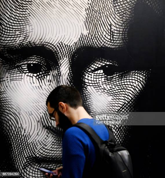A man looks at a painting depicting Russian president Vladimir Putin at the 'SUPERPUTIN' exhibition at UMAM museum in Moscow on December 6 2017 / AFP...