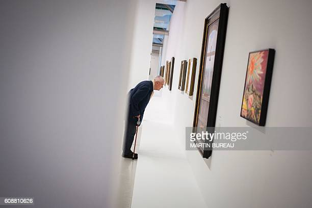 A man looks at a painting during a visit of the exhibition of Belgian painter Rene Magritte on September 20 2016 at the Georges Pompidou museum in...