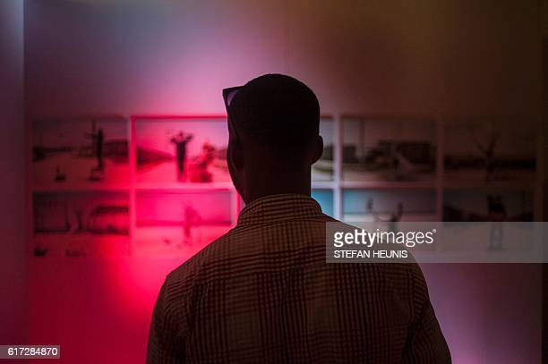 Man looks at a photography exposition during the opening of the Lagos Photo festival in Lagos on October 22, 2016. Lagos Photo was launched in 2010...