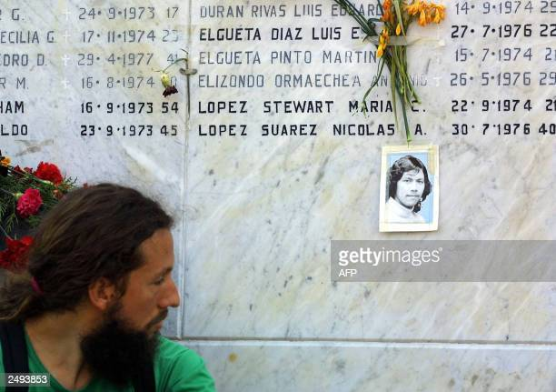 A man looks at a picture of a disappeared person at the Memorial of the Detainee and Disappeared in the General Cemetery 14 September 2003 during a...