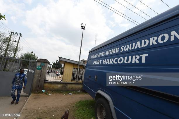 A man looks at a police antibomb vehicle parked at the main gate of the Independent National Electoral Commission headquarters in Port Harcourt...