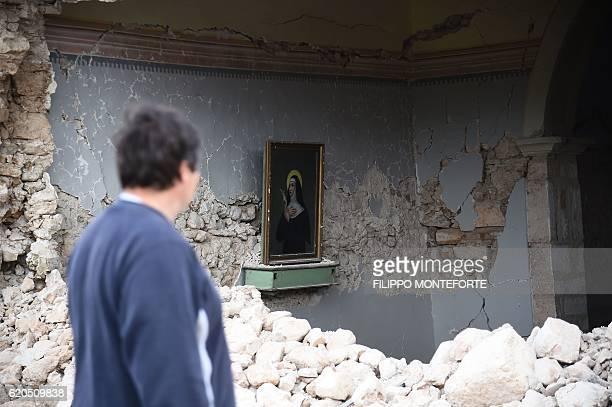 A man looks at a portrait of Santa Rita da Cascia in a small chapel partially collapsed in San Pellegrino near Norcia on November 2 2016 three days...