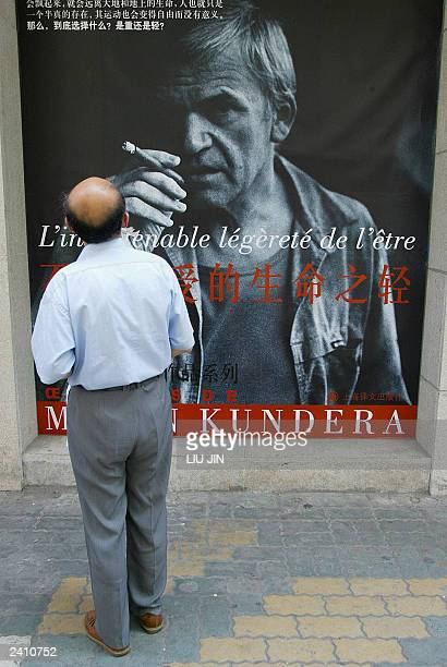 A man looks at a poster promoting the wellknown Czech writer Milan Kundera's work The unbearable lightness of being at a book store in Shanghai 19...