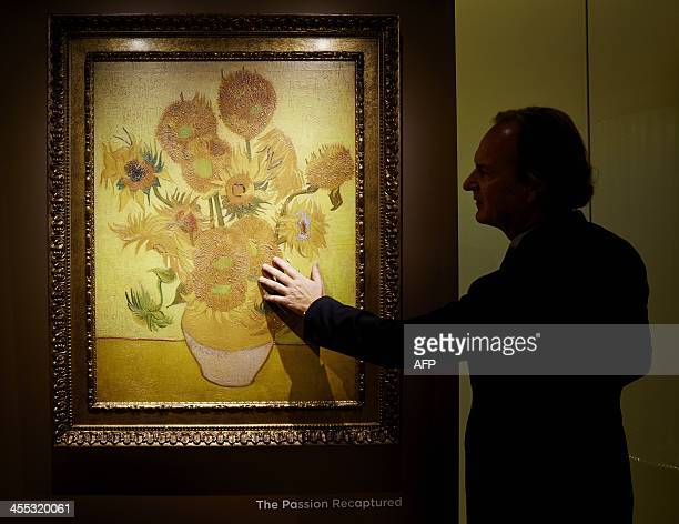 A man looks at a 'relievo' a threedimensional reproduction of the of Vincent van Gogh's The Sunflowers on December 12 2013 in Schiphol Amsterdam...