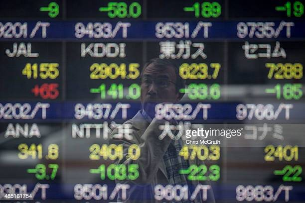 A man looks at a screen showing global stock market information on the street in Tokyo on August 25 2015 Japan's share prices dropped nearly 40...