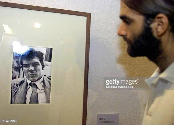 A man looks at a self portrait of Ernesto 'Che' Guevara during a exhibition of photographs that were primarily made by Guevara 16 August 2001 in...