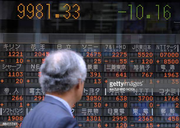 Man looks at a share prices board of the Tokyo Stock Exchange in downtown Tokyo on June 11, 2009. Japanese share prices on June 11 briefly topped the...