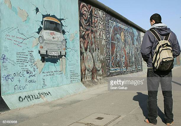 A man looks at a stillstanding section of the Berlin Wall known as the East Side Gallery on March 30 2005 in Berlin Germany According to a recent...