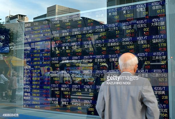 A man looks at a stock prices board showing the numbers on the Nikkei 225 at the Tokyo Stock Exchange in Tokyo on September 30 2015 The benchmark...