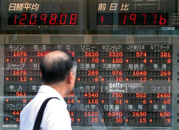 A man looks at a stock prices on a board outside a brokerage in Tokyo Wednesday August 10 2005 Japanese stocks climbed sending the Topix index to a...