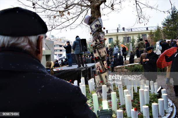 A man looks at a tree covered with candles and portraits as people gather on the spot where Turkish journalist Ugur Mumcu was assassinated during a...