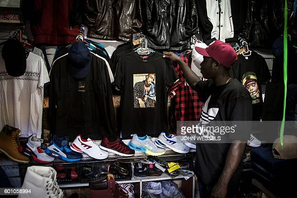A man looks at a tshirt of late rap music icon Tupac Shakur at a local market on September 9 2016 in Johannesburg September 13th will mark the 20th...