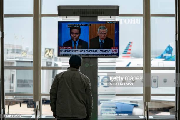 A man looks at a TV screen at Ronald Reagan Washington National Airport on March 29 in Arlington Virginia The coronavirus death toll shot past 20000...