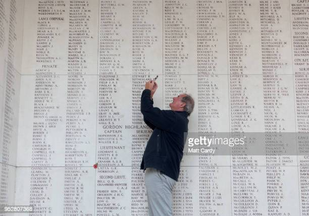 Man looks at a wall inscribed with the names of the fallen as people gather for the Last Post ceremony at the Menin Gate on April 20, 2018 in Ypres,...