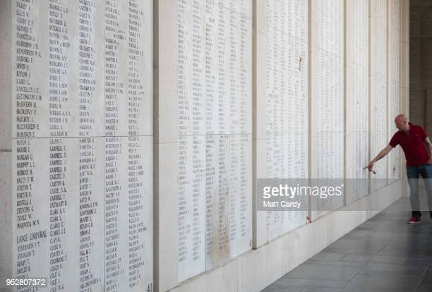 A man looks at a wall inscribed with the names of the fallen as people gather for the Last Post ceremony at the Menin Gate on April 20 2018 in Ypres...