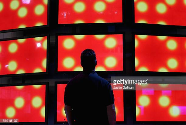A man looks at a wall of Panasonic high definition televisions on display at the 2005 Consumer Electronics Show January 5 2005 in Las Vegas Nevada...
