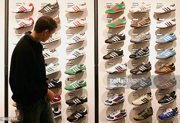 Man looks at Adidas shoes on display during the opening of the new Adidas Performance Store October 26, 2005 in Berlin, Germany. Adidas-Salomon AG is...