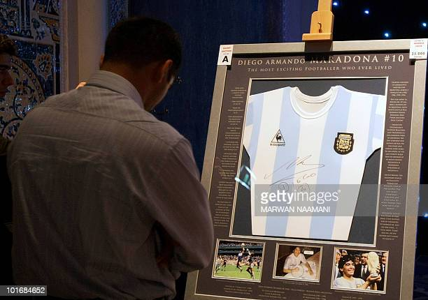 A man looks at an autographed jersey of Argentina's football legend Diego Maradona displayed for auction at a starting bid of 25000 dirhams during an...