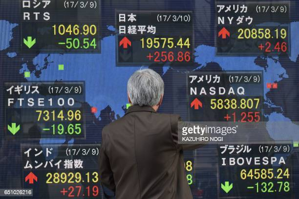 A man looks at an electric quotation board flashing numbers of the world's stock markets including the Tokyo Stock Exchange in front of a securities...