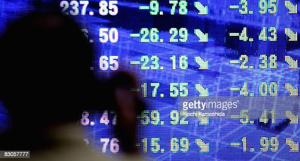 A man looks at an electronic board displaying falls in share prices on September 30 2008 in Tokyo Japan The 225issue Nikkei Stock Average drops...