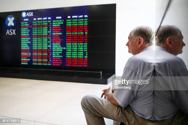 A man looks at an electronic board displaying stock information at the Australian Securities Exchange operated by ASX Ltd in Sydney Australia on...