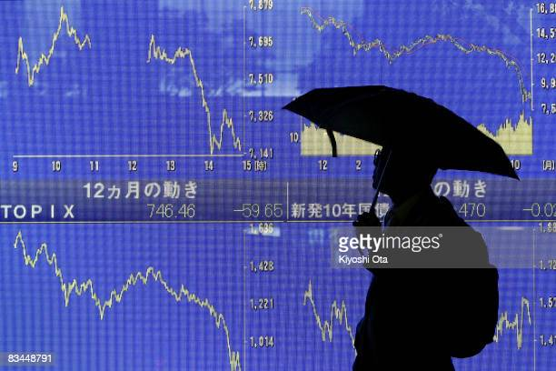 A man looks at an electronic board showing the downward trend of Japan's Nikkei share average on October 27 2008 in Tokyo Japan The 225issue Nikkei...