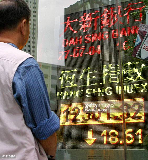 A man looks at an electronic monitor showing the Hang Seng Index in Hong Kong 27 July 2004 The key Hang Seng index closed down 1851 points at 1230132...