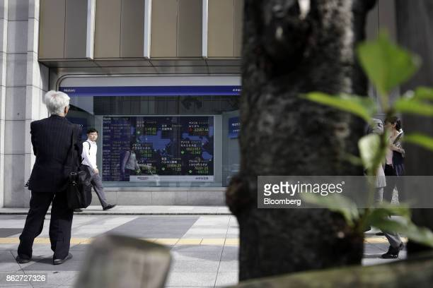 A man looks at an electronic stock board outside a securities firm in Tokyo Japan on Wednesday Oct 18 2017 As Prime Minister Shinzo Abe's ruling...