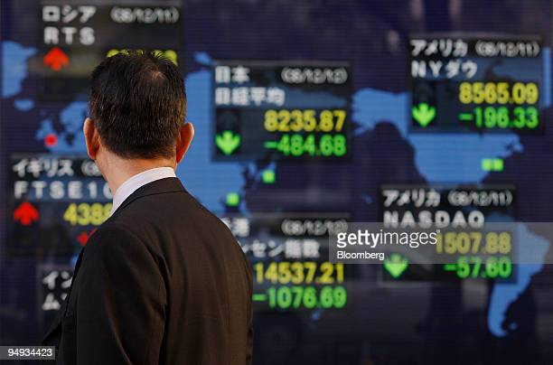 Man looks at an electronic stock board outside a securities firm in Tokyo, Japan, on Friday, Dec. 12, 2008. Japanese stocks plunged, retreating for...