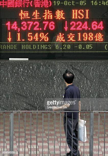 A man looks at an electronic stock price index in Hong Kong 19 October 2005 Hong Kong share prices slumped 19 October shedding 154 percent on Wall...