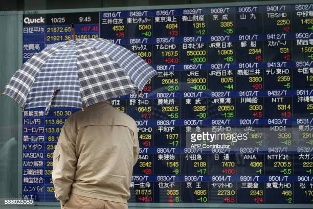 A man looks at an electronics stocks indicator displaying numbers of the Tokyo Stock Exchange in Tokyo on October 25 2017 Tokyo stocks opened higher...