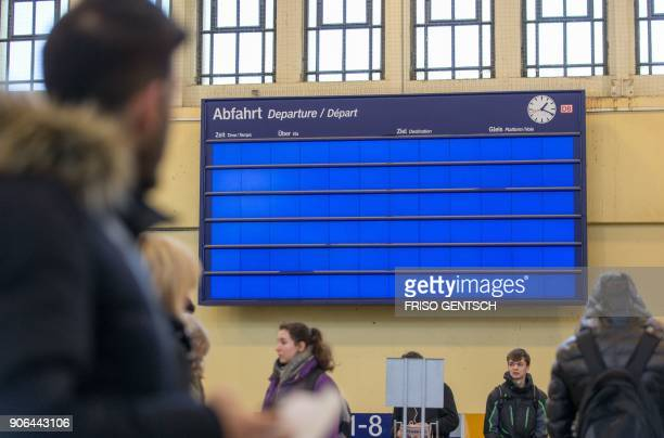 A man looks at an empty schedule information board in the central train station in Bielefeld western Germany on January 18 2018 German rail says...