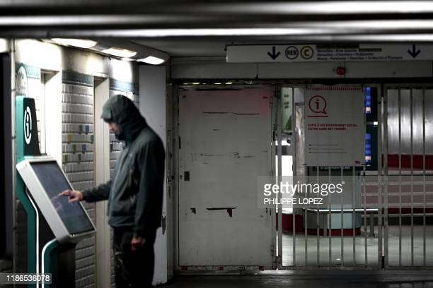 """Man looks at an information board on December 5, 2019 at Saint-Michel metro and regional train RER station in Paris next to a sign reading """"The..."""