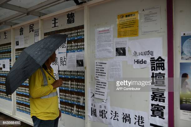 A man looks at anti independence posters displayed after pro independence posters were displayed at the Chinese University of Hong Kong university...